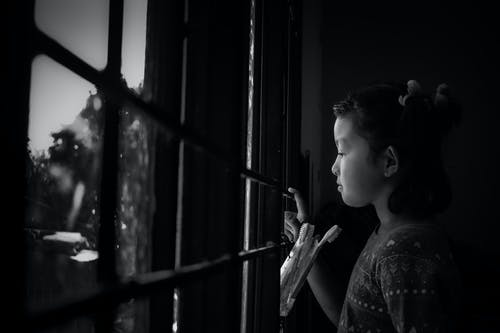 Thoughtful ethnic child looking through window in rain