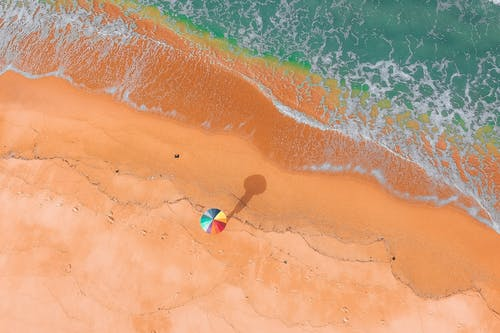 Aerial View Person With Colorful Umbrella on Beach