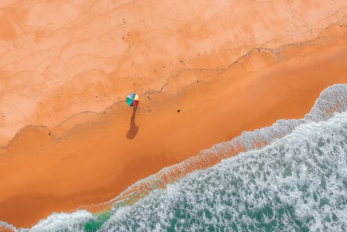 Top View Photo of Person Holding Colorful Umbrella on Beach