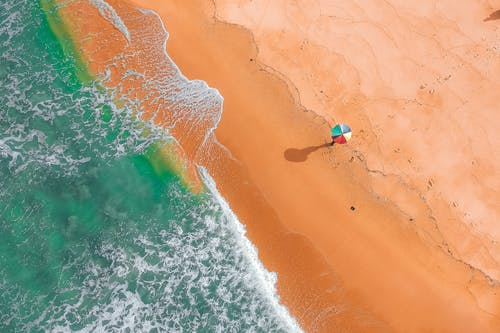 Aerial View of Person Holding Colorful Umbrella on Beach