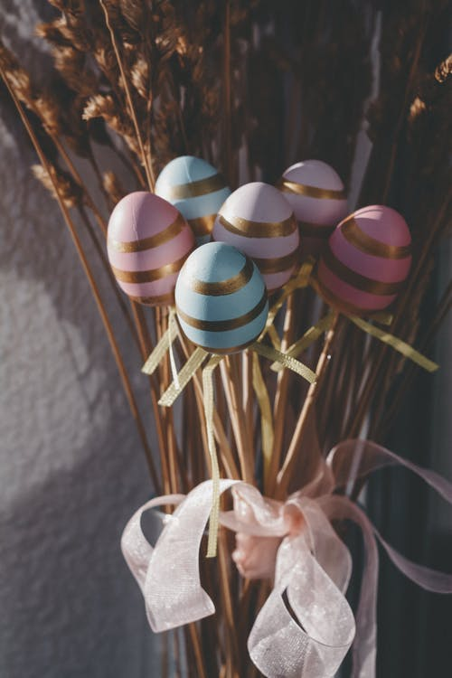 High angle of festive bouquet with colorful Easter eggs and dry wheat spikelets tied with pink ribbon