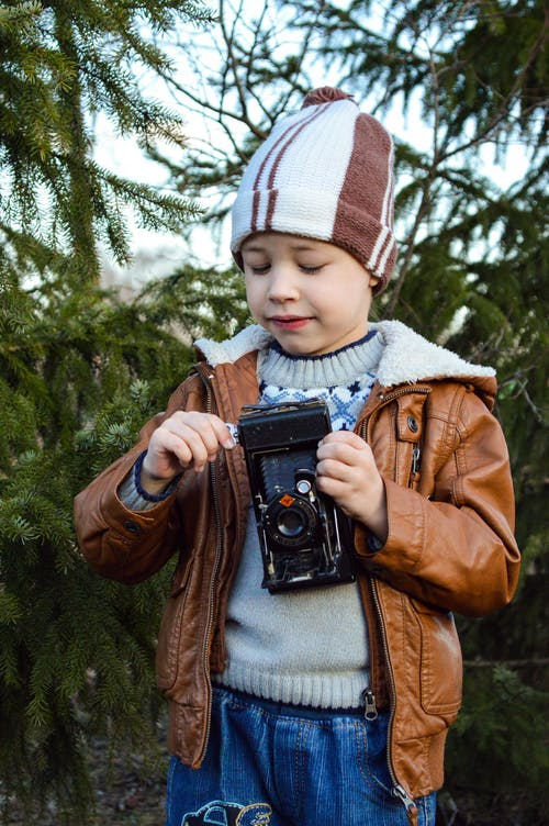 Joyful little boy in warm outerwear and hat playing with vintage film camera while resting in park with evergreen trees