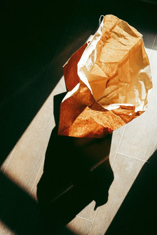 From above of recycling kraft paper sack placed on tiled floor on sunny day