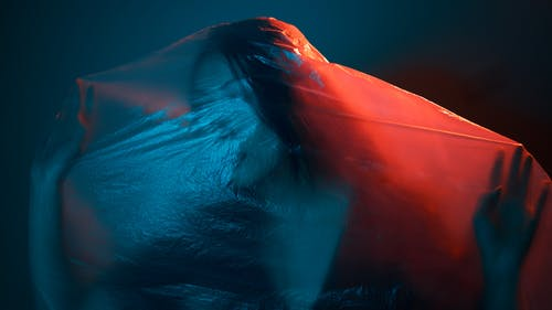 Unrecognizable female wrapped with translucent plastic bag in dark room with neon lights
