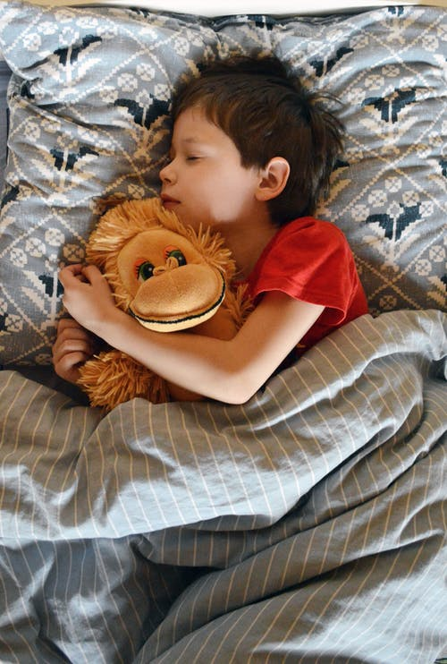 Cute child hugging toy and sleeping in bed