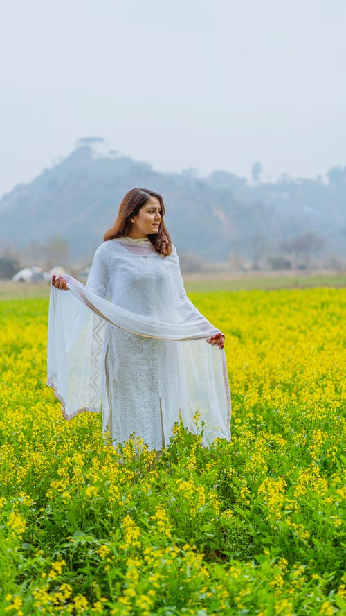 Young ethnic woman standing in blooming field with yellow flowers