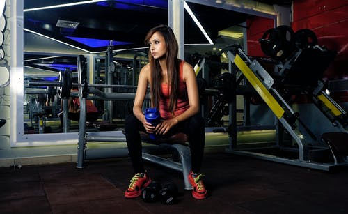 Full length of tired fit young ethnic female in sportswear sitting on bench in gym with water bottle while resting during workout