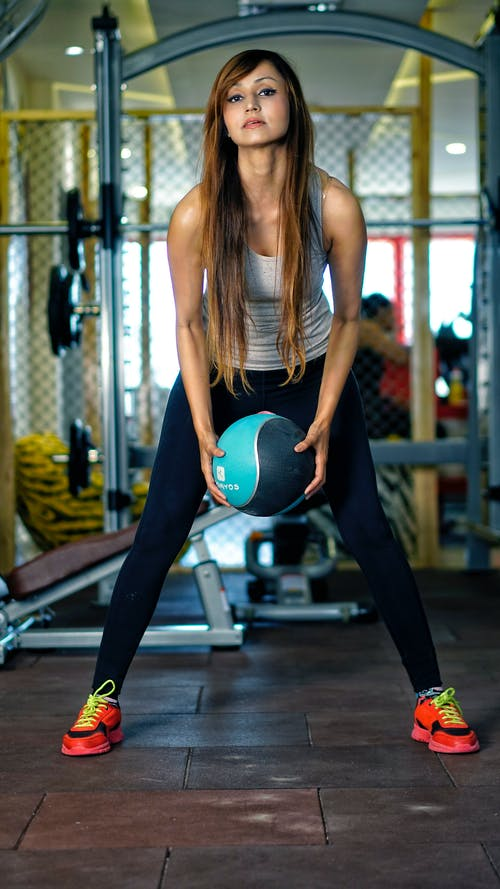 Strong young ethnic sportswoman exercising with ball in gym