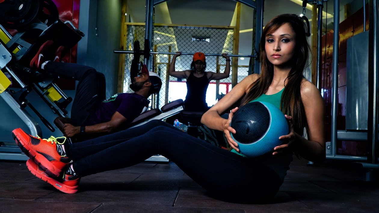 Serious young ethnic woman doing abs workout in sports studio