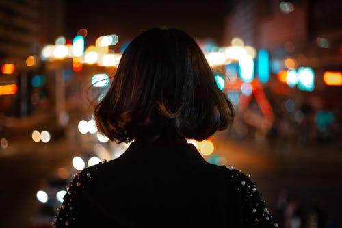 Woman in Black Top Looking at the City Lights