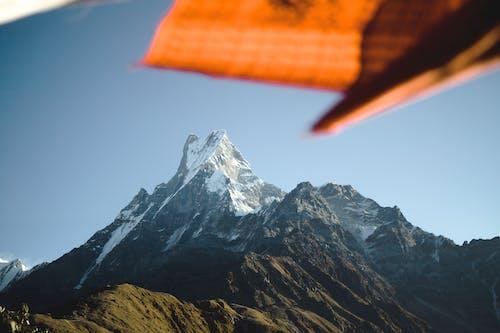 Orange and White Flag on Top of Mountain