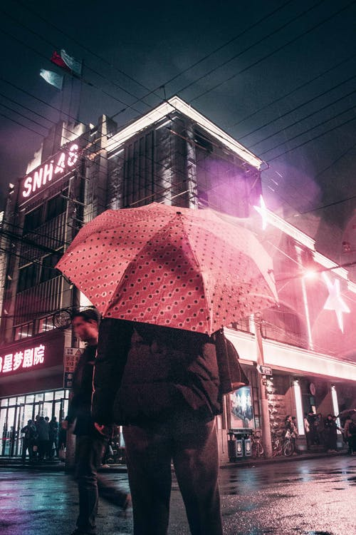 Person in Black Coat Holding Red Umbrella Walking on Street during Nighttime