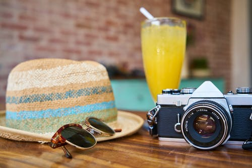 Gray and Black Dslr Camera Beside Sun Hat and Sunglasses