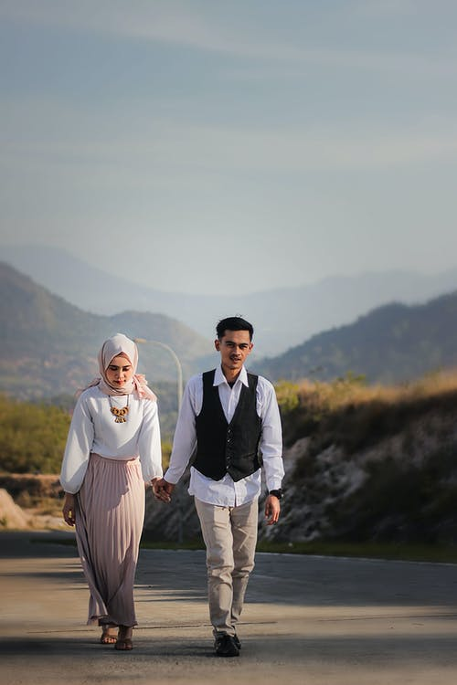 Married muslim couple walking on road along mountains