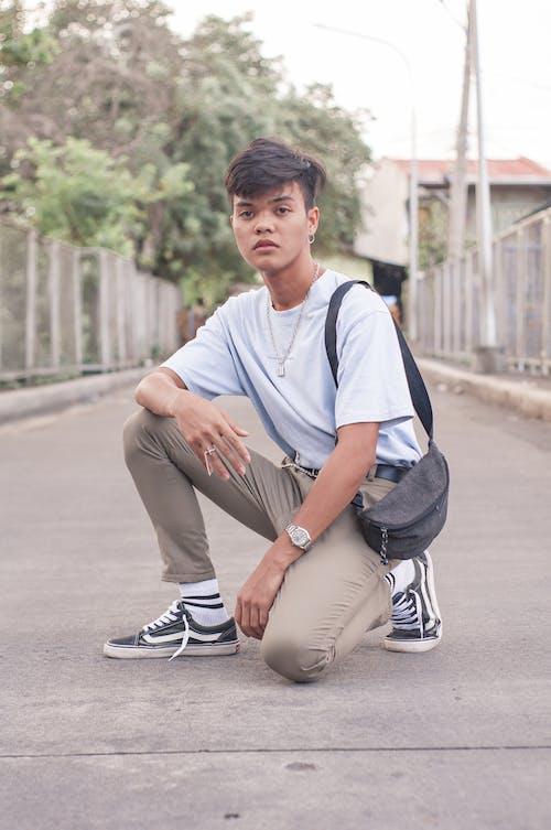 Unemotional teenager squatting on street