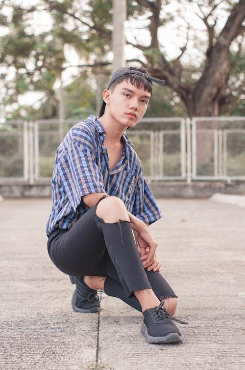 Stylish young ethnic teenager sitting on squat on street