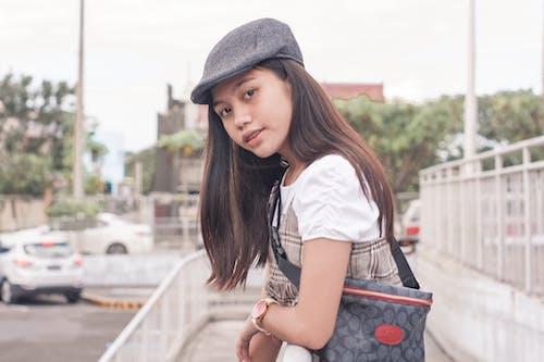 Stylish Asian teenager standing on street on daytime