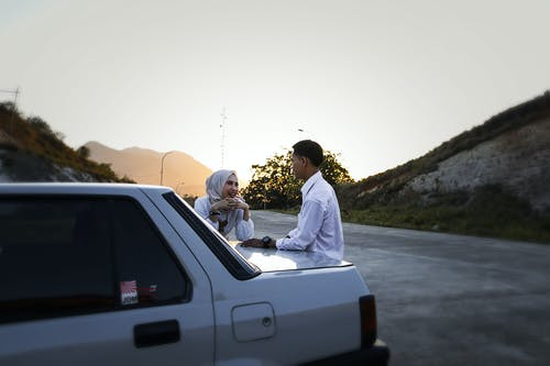 Young ethnic man and woman standing near car trunk and speaking with each other while resting during trip in highland at sunset