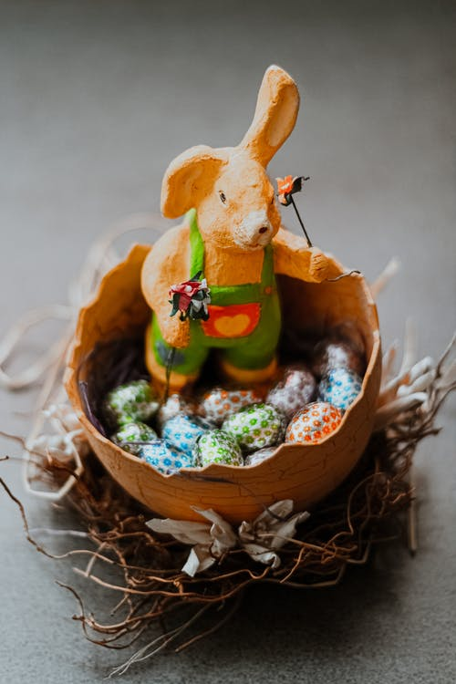 Easter bunny with tiny eggs in bowl on twigs nest