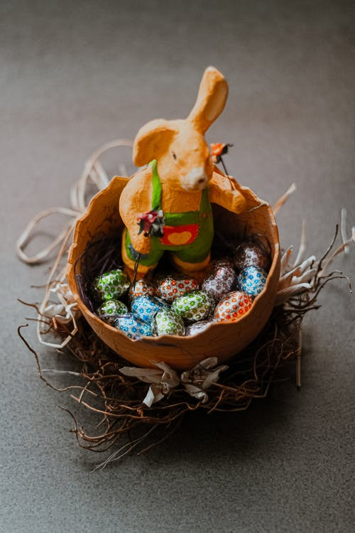 Close-Up Shot of Rabbit Figurine and Chocolate Eggs