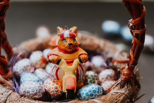 Close-Up Shot of Rabbit Figurine and Chocolate Eggs on a Basket