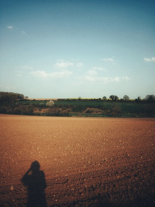Shadow of anonymous person on plowed field near green meadows against blue sky on sunny summer day