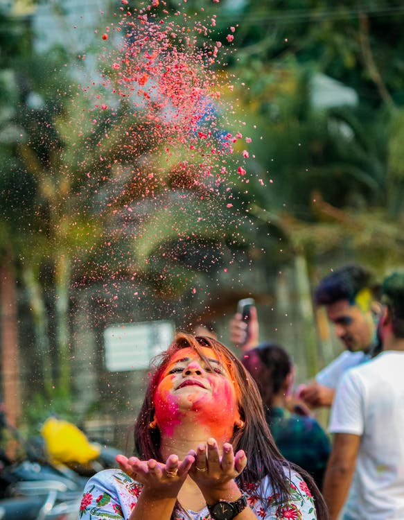 Indian woman with painted face throwing Holi paints in air
