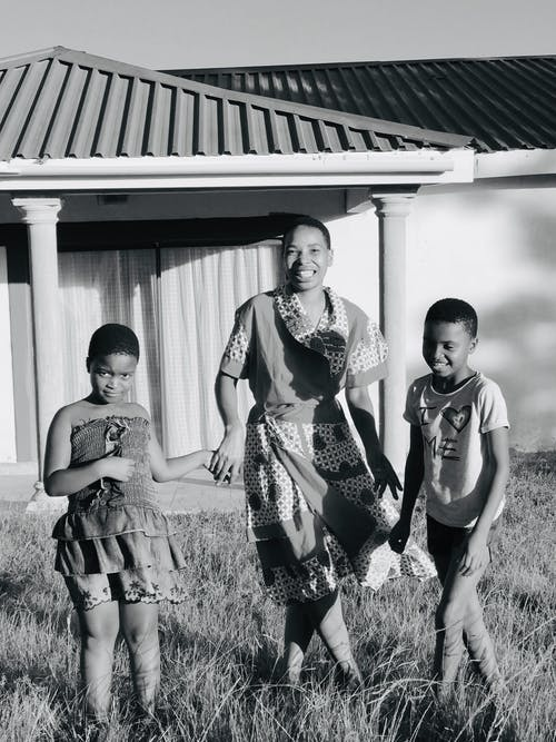 Black and white full body joyful African American female in casual dress holding hands with cute positive children and standing together in backyard of cozy house