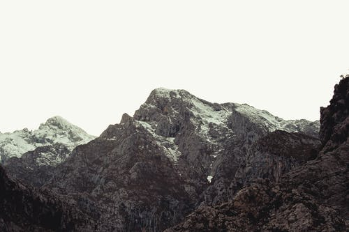 Scenic view of majestic snowy mountains with dry random vegetation under gray winter sky