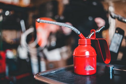 Red steel small ink bottle with pipe for retro printing machine placed on table in craftsmanship