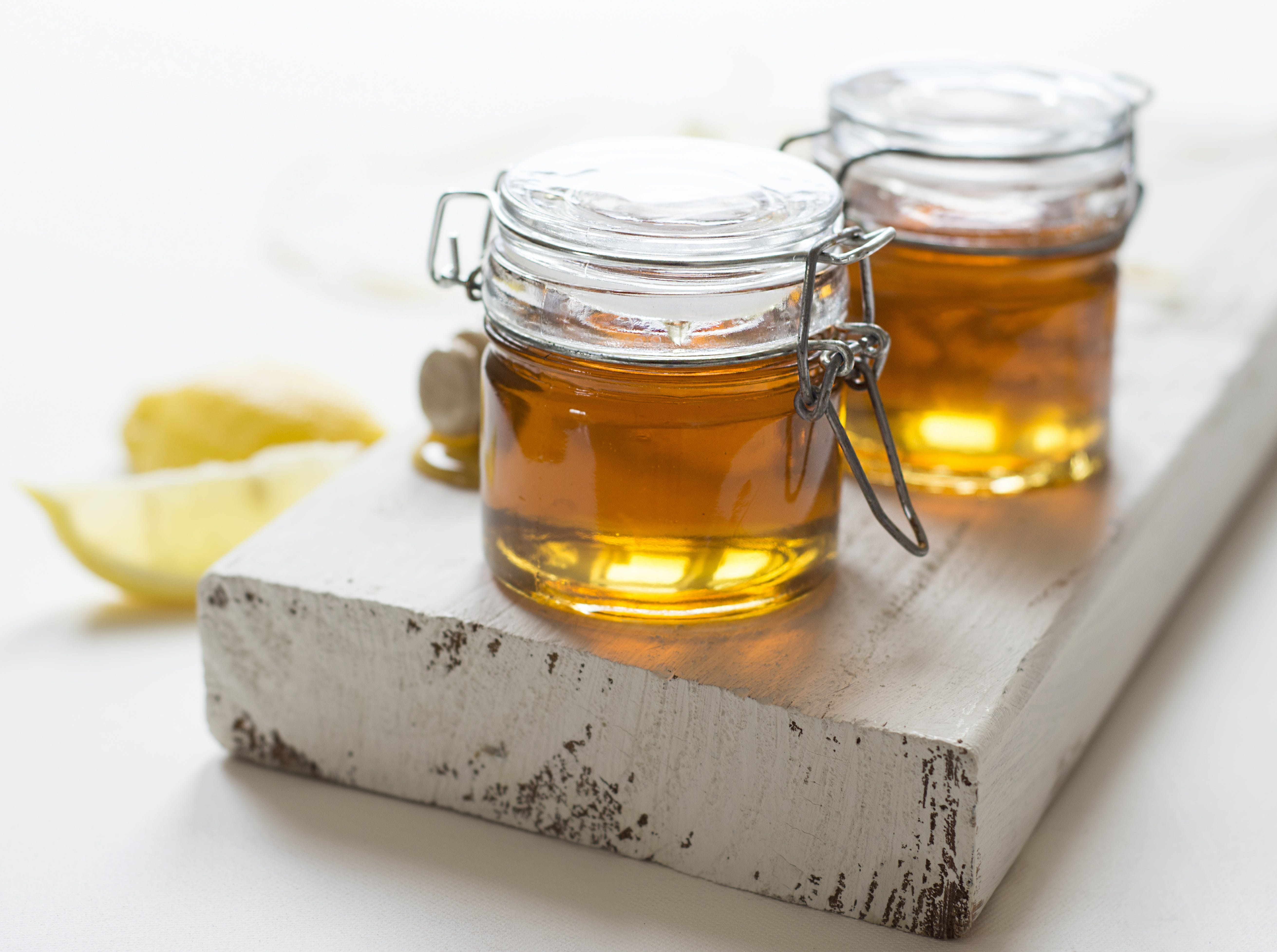 Two Clear Glass Jars of Oils on Wooden Plank