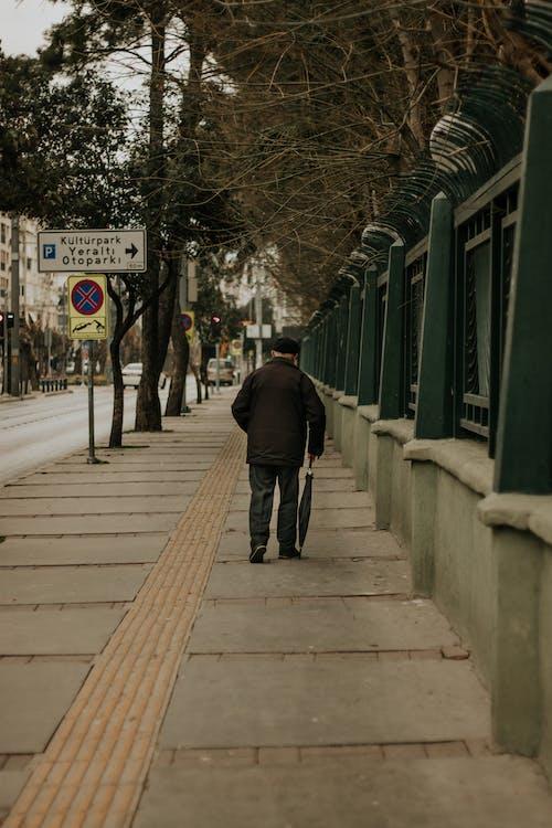 Man in Black Jacket Walking on Wooden Bridge