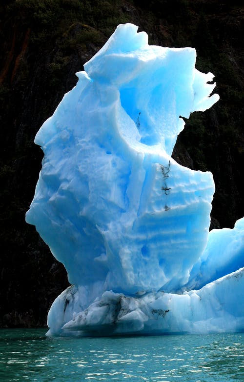 Iceberg Floating on Water Near Cliff