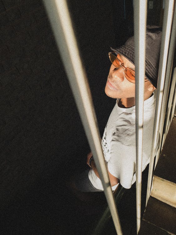 High angle pensive young African American male in casual clothes and sunglasses leaning on metal bars in dark room and looking away thoughtfully