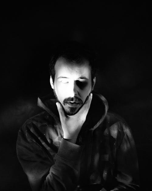 Black and white of melancholic bearded young male in hoodie touching chin with closed eyes against dark background