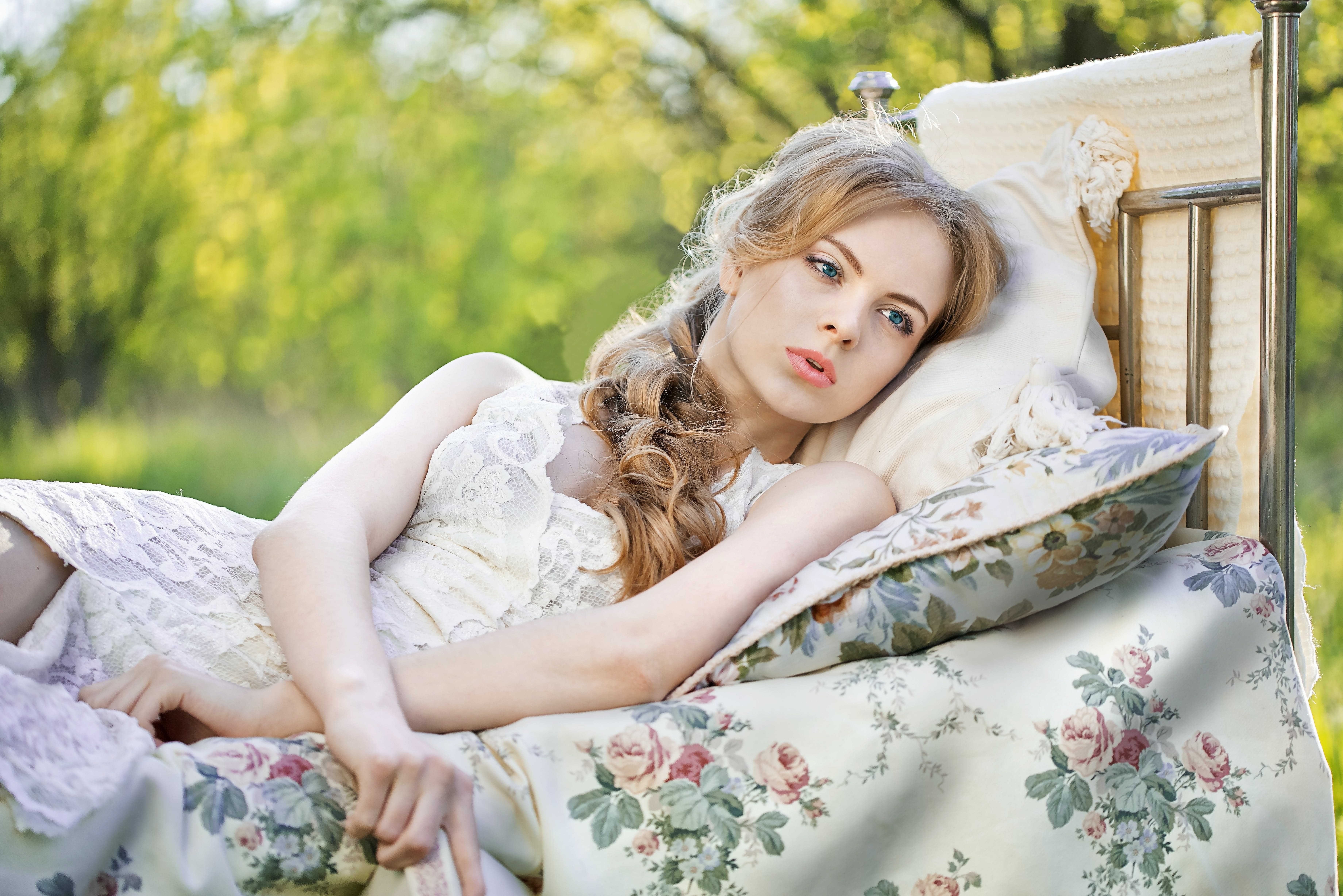 Woman Lying on Blue and White Floral Bed Sheet