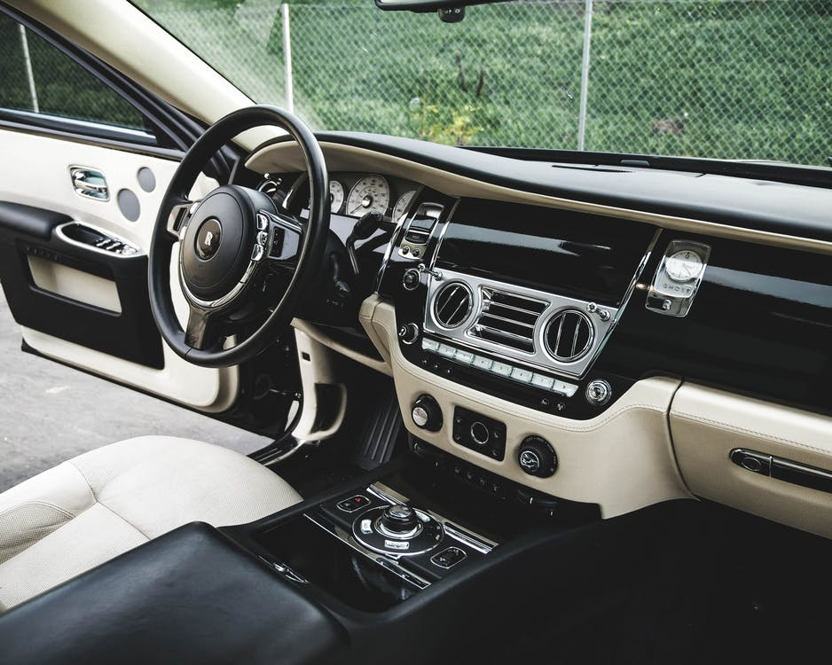 Expensive luxury car interior with white leather seats and shiny dashboard