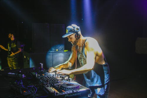 Focused DJ performing techno music on sound mixer in nightclub