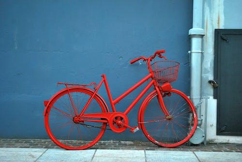 Red bike parked on sidewalk near wall