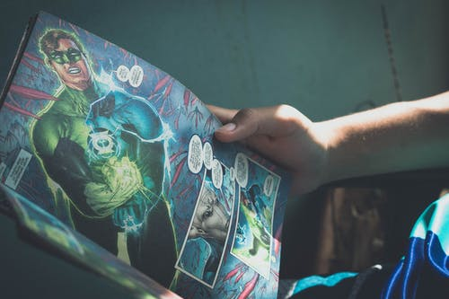 Crop person reading story about superhero