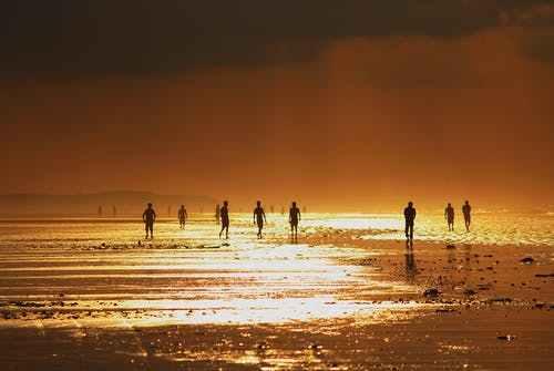 Anonymous peoples enjoying seascape during sunset on shore