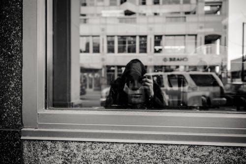 Unrecognizable person taking shot of shop window standing on sidewalk