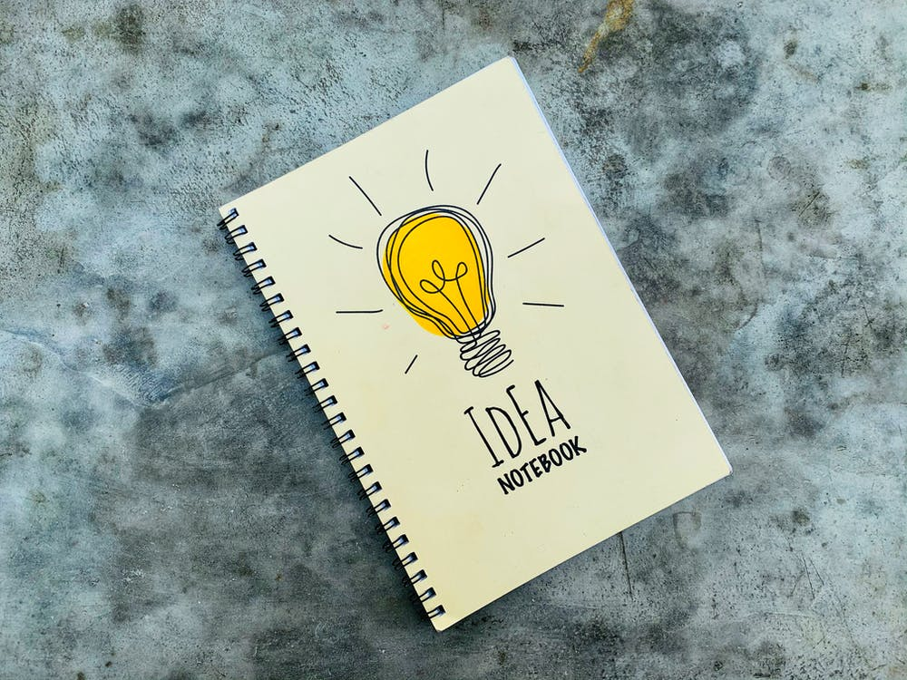 Top view of creative spiral notebook with yellow light bulb illustration on cover placed on gray table