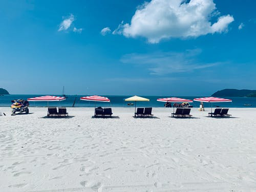 Sandy beach with loungers and umbrellas on sunny day