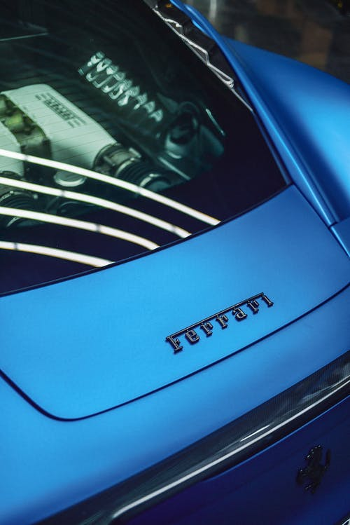 From above of brand name and emblem of luxury Italian automobile manufacturer on new posh blue sports car