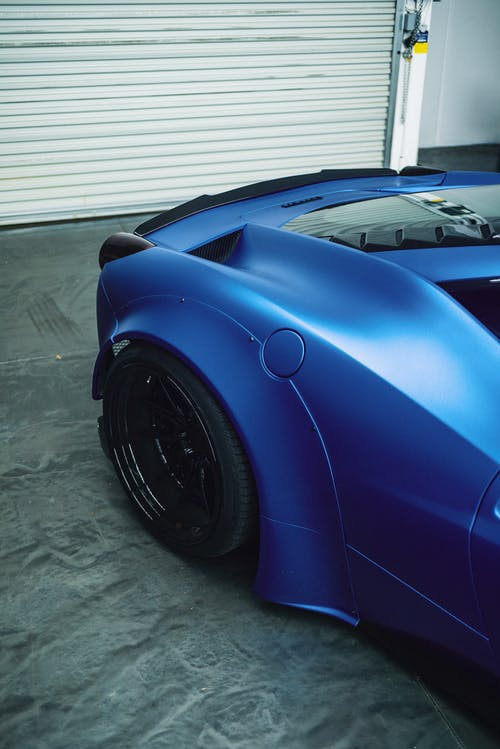 High angle of tire and back window of fashioned expensive blue coupe car parked in garage