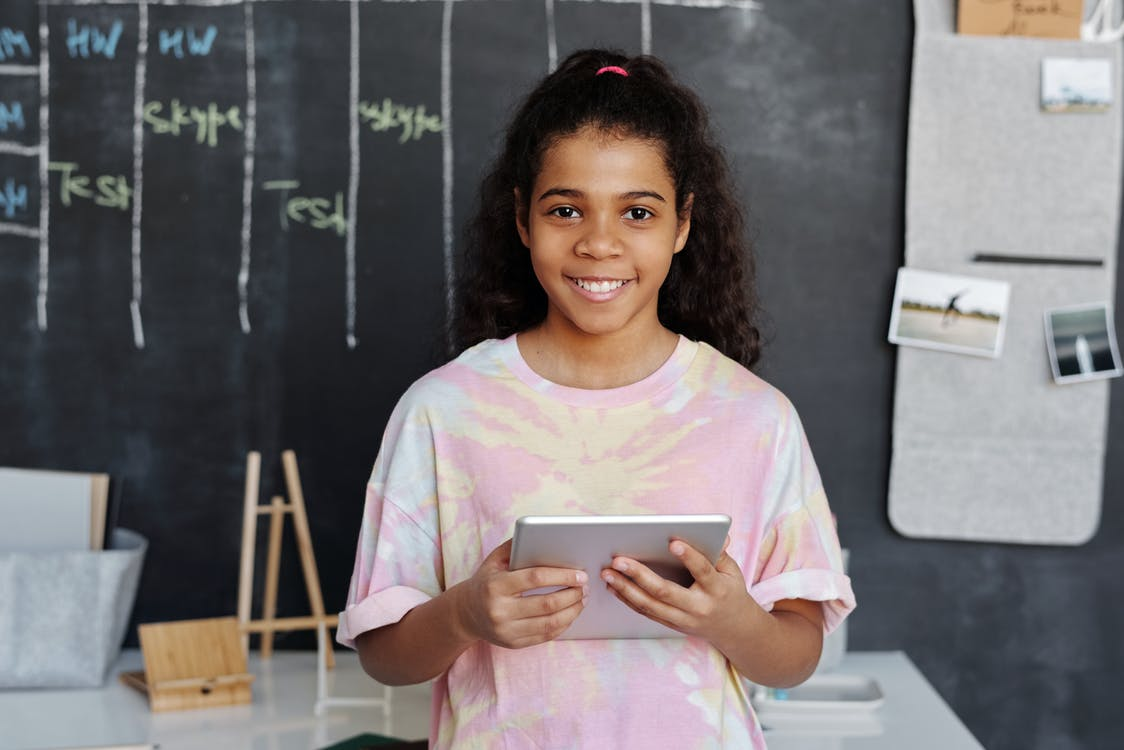 Woman in Pink Crew Neck T-shirt Holding Tablet Computer