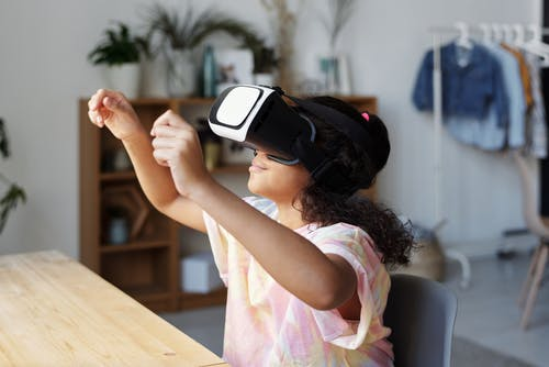 Girl in Pink Shirt Wearing Black and White Vr Headset
