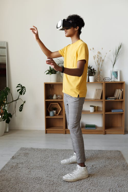 Boy in Yellow T-shirt and Gray Pants Standing on Gray Carpet
