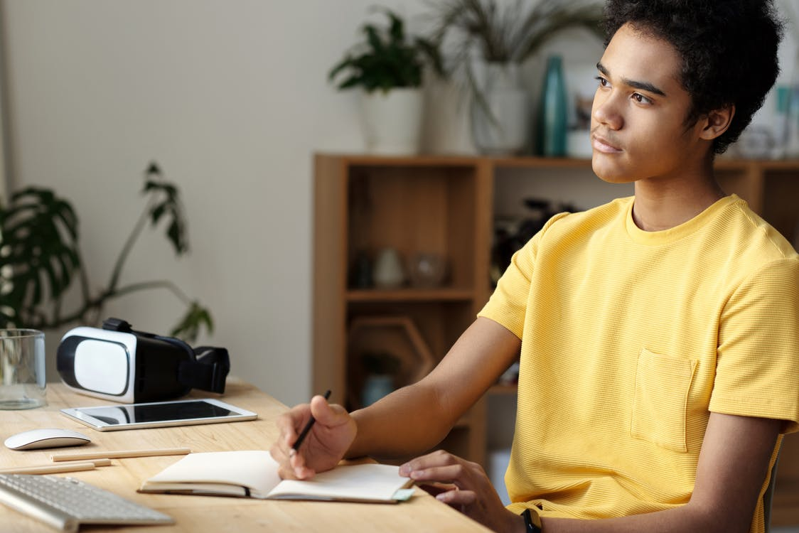 Boy in Yellow Crew Neck T-shirt Writing on White Paper